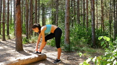 Woman girl buckling her shoes before running jogging in park, wood, forest Stock Footage