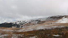 Clouds move rapidly over snowy mountain brown grass blowing foreground Stock Footage