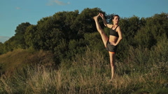 Woman practicing yoga in the park at sunset Stock Footage