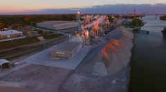Aerial flyover of scenic industrial complex with lights, early morning Stock Footage