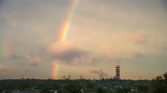 Clouds in the Sky and Rainbow are Moving over the City, buildings and Plant Stock Footage