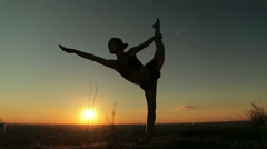 Woman practicing yoga in the park at sunset - lord of the dance pose Stock Footage