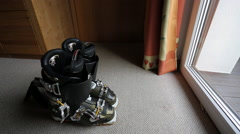 Skier grabs ski boots off the floor and leaves the room. Stock Footage