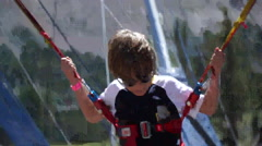 A young boy bouncing on a bungee trampoline outdoors at a mountain resort. Stock Footage