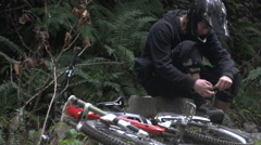 A mountain biker tying hi shoes while on a trail in a forest, super slow motion. Stock Footage