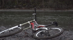 A mountain biker picking bike off rocky ground with a river in the background, s Stock Footage