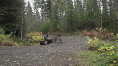 A mountain biker tying his shoes while resting by his bike in a scenic forest, s Stock Footage