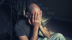 bald man fired crying with his head in his hands Stock Footage