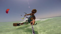 A young man kitesurfing in a tank top on a sunny day in Egypt, slow motion. Stock Footage