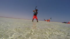 A young man kitesurfing in a tank top on a sunny day in Egypt. Stock Footage