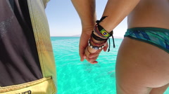A young man and woman holding hands while jumping off of a boat into the ocean. Stock Footage