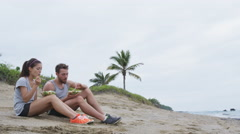 Happy young people eating healthy salad for lunch on beach laughing together Stock Footage