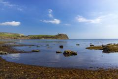 Calm waters of Kimmeridge Bay reflect views of Clavell's Tower under blue ski Stock Photos