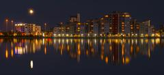 The moon and cityscape lights, reflect off harbour waters, poole Stock Photos