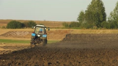 Farm tractor plowing the field, leaving behind a cloud of dust Stock Footage