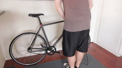 A young man pumping up his bike tires inside his apartment. Stock Footage