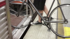 A young man taking his bike onto the metro train. Stock Footage