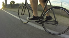 POV tracking shot of a young man riding his bicycle on a bike path by a creek at Stock Footage