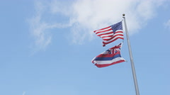 Hawaii State flag and American flag of USA waving on blue hawaiian sky Stock Footage