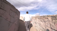 A young man freerunner doing parkour and flips over stone wall. Stock Footage
