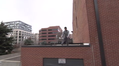 A young man freerunner doing parkour and flips off of a roof in city park. Stock Footage