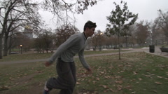 A young man freerunner doing parkour and running in a city courtyard. Stock Footage