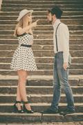 Loving couple retro style flirting on stairs Stock Photos