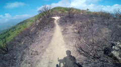POV of a man mountain biking through a burned down European forest in the mounta Stock Footage