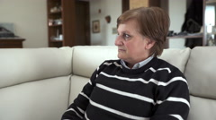 Elderly woman sitting on a white sofa looking at the camera Stock Footage