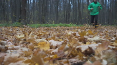 Man jogging cross country running on trail in forest. Training and exercising Stock Footage