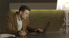 Businessman looking with amazement at his laptop computer Stock Footage