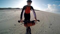 POV of a man falling off his bike on a European beach. Stock Footage