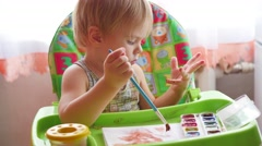 Little child draws paints on a sheet of paper Stock Footage