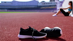 Desperate disappointed track runner athlete woman at a stadium, shoes in front Stock Footage