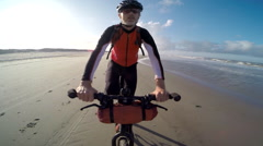 POV of a man falling off his bike on a European beach. Stock Footage