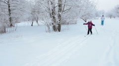 Russian family with mom and daughter skiing in urban park at winter season Stock Footage