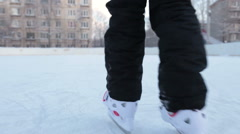 Close up rear view at children legs in white plastic hockey skates riding ice Stock Footage