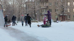 Adults and children sledge down from ice hill with inflatable sledges. Winter Stock Footage
