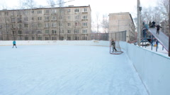 Hockey ice rink with boys playing game is near wooden ice-hill, Russia Stock Footage