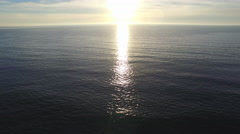 Aerial shot of the sun setting over a beach and ocean horizon. Stock Footage