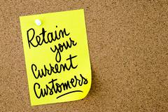 Retain Your Current Customers text written on yellow paper note Stock Photos