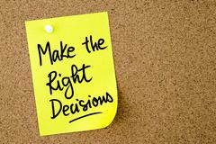 Make The Right Decisions text written on yellow paper note Stock Photos