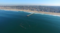 Aerial shot of surfers paddling out on the ocean. Stock Footage