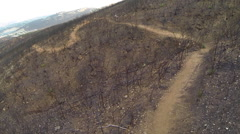 Aerial shot of young man mountain biking down a hillside trail. Stock Footage