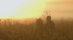Silhouettes of men and women in the dry grass. Slow motion. Stock Footage