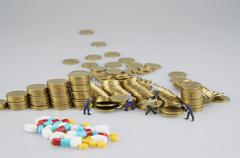 Stack of gold coin with miniature people and blur medicine Stock Photos