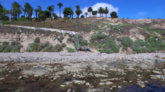 Aerial shot of a young man running stairs on the side of a cliff by the ocean. Stock Footage
