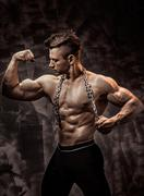 The Perfect male body - Awesome bodybuilder posing. Hold a chain with tattoo Stock Photos