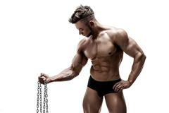 Strong bodybuilder doing exercise with metal chain Stock Photos