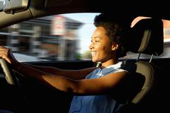 Happy young african woman driving a car Stock Photos